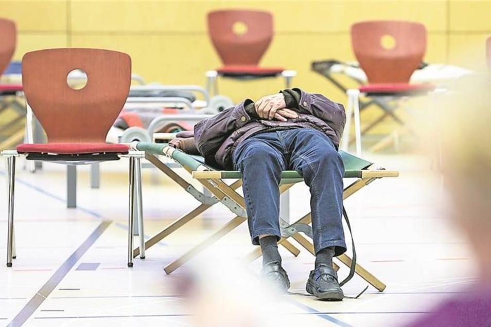 Ein Evakuierter entspannt sich auf einem Feldbett in der Turnhalle der Martin-Anderson-Nexö-Gymnasiums.