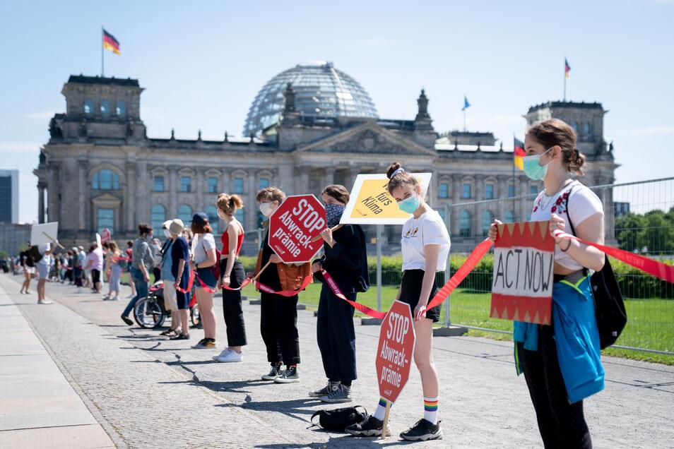 Menschen demonstrieren am Dienstag vor dem Bundeskanzleramt gegen eine mögliche Abwrackprämie und für das Klima, während die Spitzen der großen Koalition über ein Konjunkturpaket und weitere Strategien im Kampf gegen das Coronavirus beraten.
