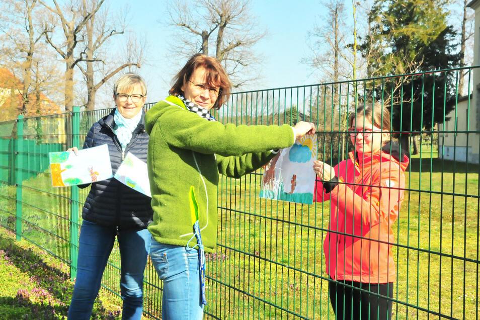 Andrea Schurig und Petra Herrmann bringen mit Marie (13) selbst gestaltete Osterbilder an. Auf dem Weg zum Park soll eine kleine Galerie den Kontakt zu Spaziergängern herstellen und sie erfreuen.