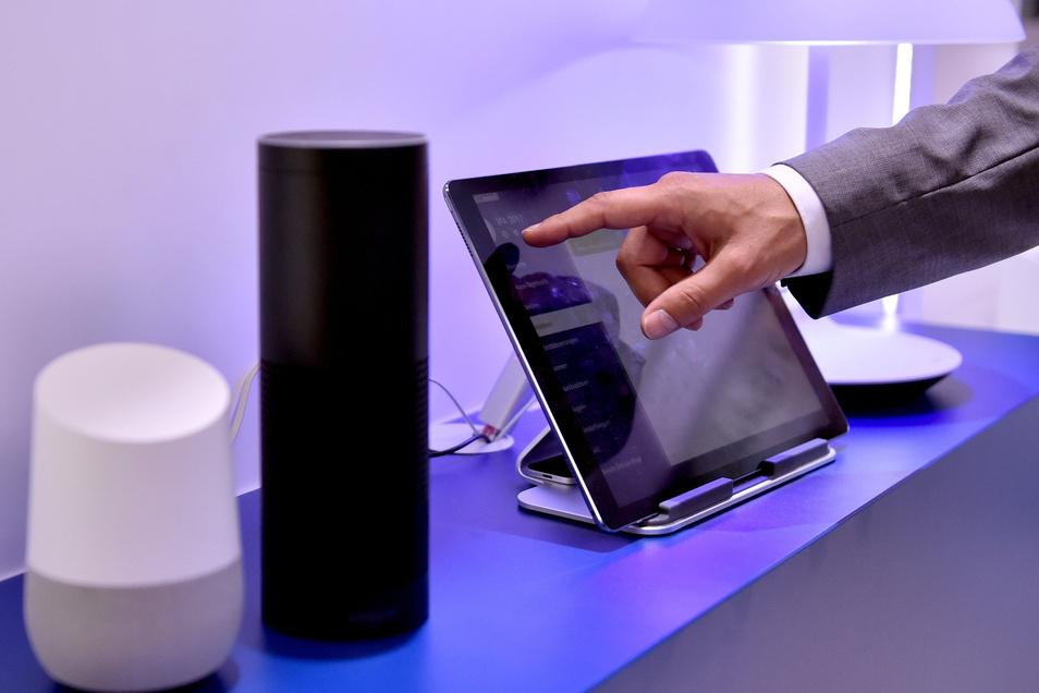 Die Lautsprecher Google Home und Amazon Echo, ausgestattet mit den  Sprachassistenten Google Assistant und Alexa, stehen gemeinsam mit einem Tablet auf der Internationalen Funkausstellung IFA in Berlin (Symbolfoto).