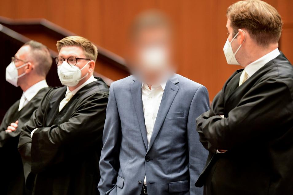 Einer der vier Angeklagten (2.v.r) steht zu Prozessbeginn in der Stadthalle Braunschweig.