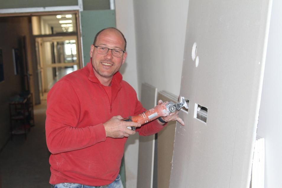 Tino Bernd von der Firma Innenausbau Saupe bereitet eine Platte zum Einbau vor. Neben den Trockenbauern sind derzeit Elektriker und Heizungsbauer in der Grundschule Waldheim aktiv.