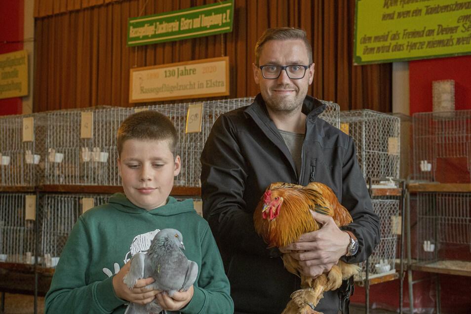 Sie freuen sich, dass sie ihre Tiere am Wochenende zeigen können: der neunjährige Carlo Hergesell mit einer Luchstaube und der zweite Vorsitzende des Elstraer Rassegeflügelzuchtvereines Daniel Böhm mit einem Brahma-Hahn.