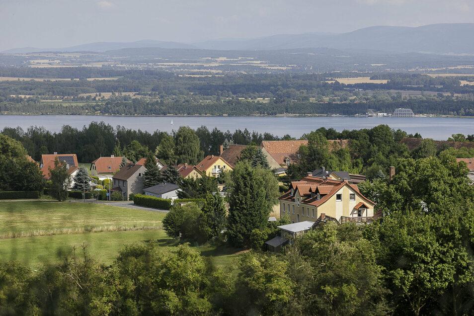 Blick auf Häuser an der Dorfstraße und Wiesenmühlweg in Jauernick-Buschbach. Dahinter ist der Berzdorfer See zu sehen.