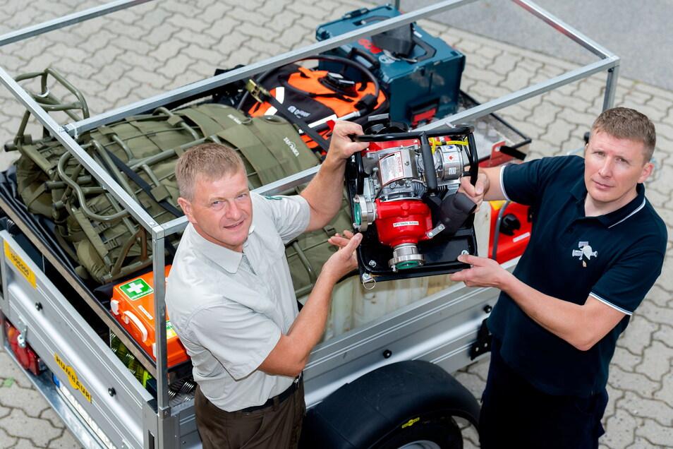 Nationalparkwächter Frank Kowalzik (li.) und Dominique Weidensdörfer von der Feuerwehr Ottendorf testen den neuen Waldbrandanhänger. Die kleine Pumpe ist auch im Gelände gut zu transportieren.