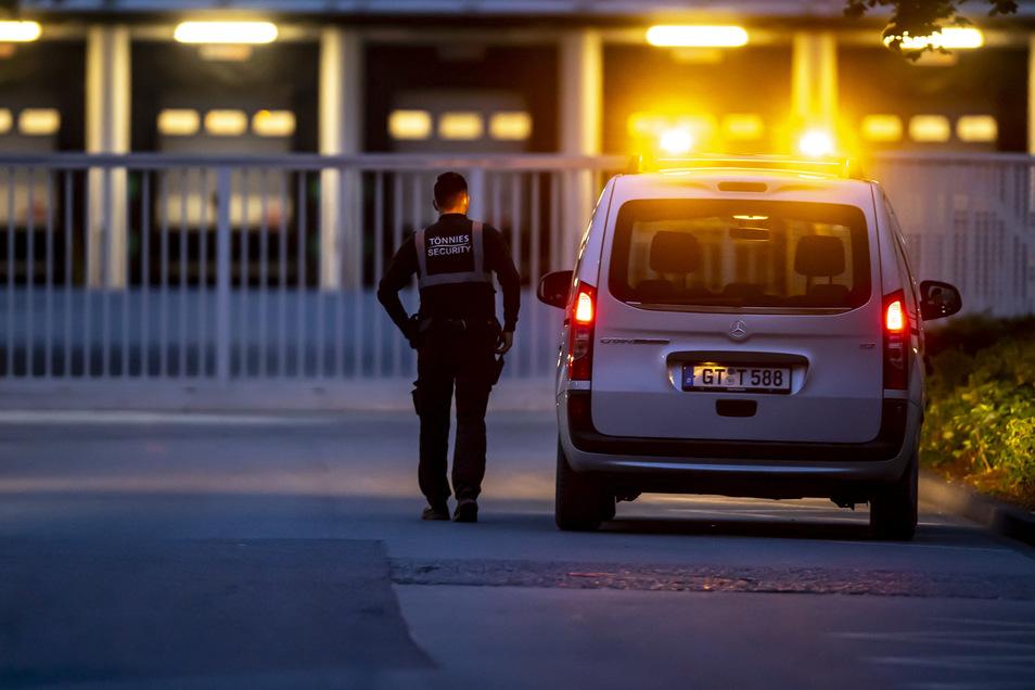 Ein Mitarbeiter einer Sicherheitsfirma geht neben einem Fahrzeug über das Firmengelände des Fleischwerks Tönnies.