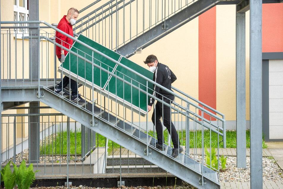 Mitarbeiter der Radebeuler Firma Manig und Palme transportieren eine alte Kreidetafel aus der Oberschule Schönfeld die Treppen herunter.