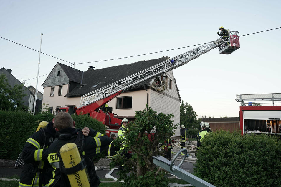 Feuerwehrleute sichern das beschädigte Wohnhaus