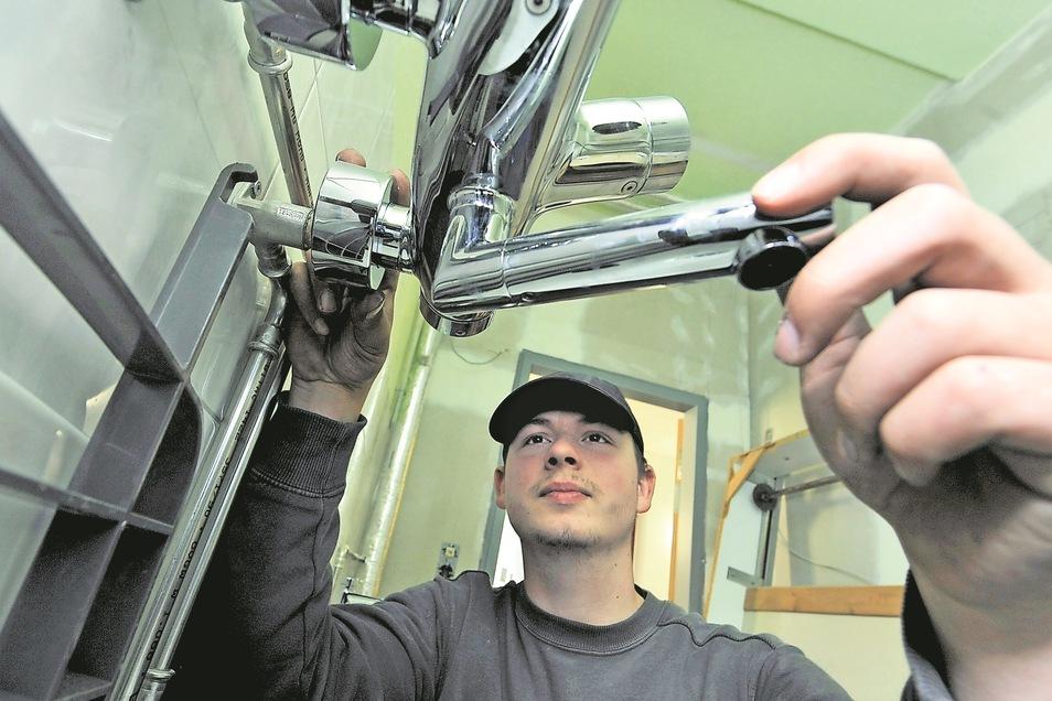 Im Neubau Schule sind derzeit Elektriker und Klempner tätig. So, wie Praktikant Kenny Gerbitz, der eine Garnitur anein Waschbecken montiert.