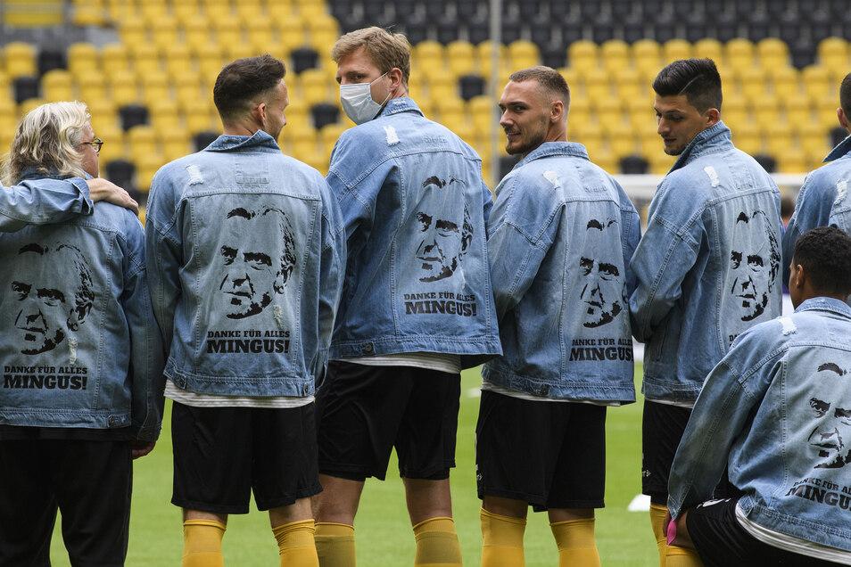 Die Mannschaft verabschiedet sich auf ihre Weise von Sportchef Minge, dessen Jeansjacke in Fußball-Dresden mittlerweile Kult-Charakter hat. Ein Duplikat mit Aufschrift tragen die Spieler bei der Erwärmung.