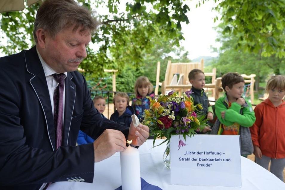 OB Bert Wendsche zündet vor der Spielplatzeinweihung eine Hoffnungskerze für Karl-Erivan Haub an.