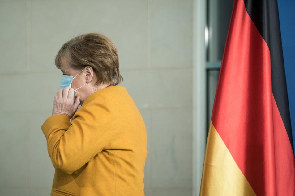 Bundeskanzlerin Angela Merkel (CDU) setzt ihre Maske auf und geht nach ihrem Statemant weg.