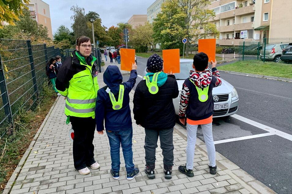 Leon, Tim und Omar zeigen die Rote Karte. Ein Auto steht im Parkverbot, direkt vor der Curie-Grundschule.