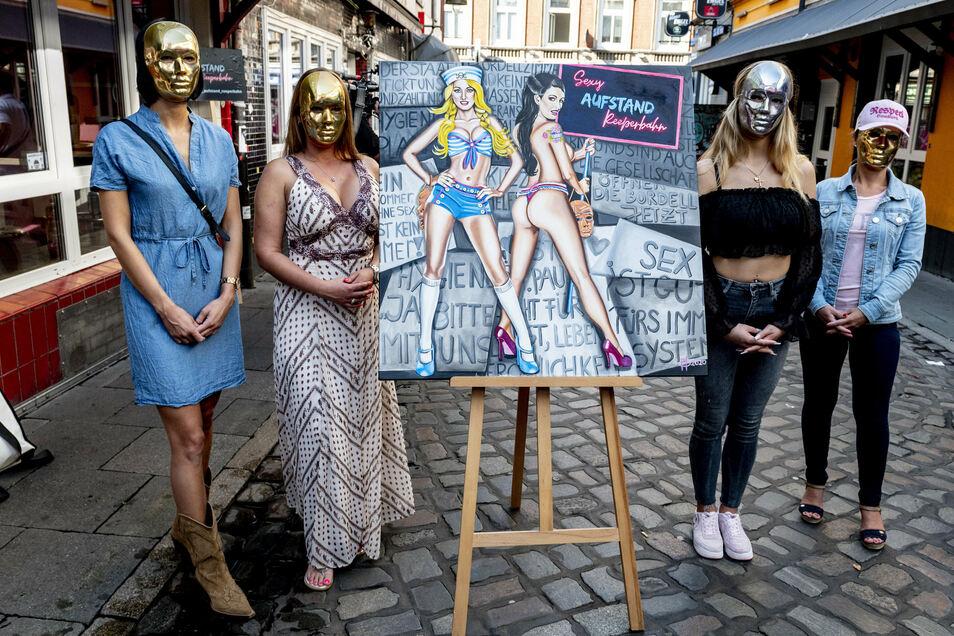 Sexarbeiterinnen warten in der Herbertstraße auf die Wiedereröffnung der Bordelle. In der Mitte steht das Gemälde der niederländischen Pop Art-Künstlerin Maaike Dirkx, auf der sie die Gruppe Sexy Aufstand Reeperbahn verewigt.