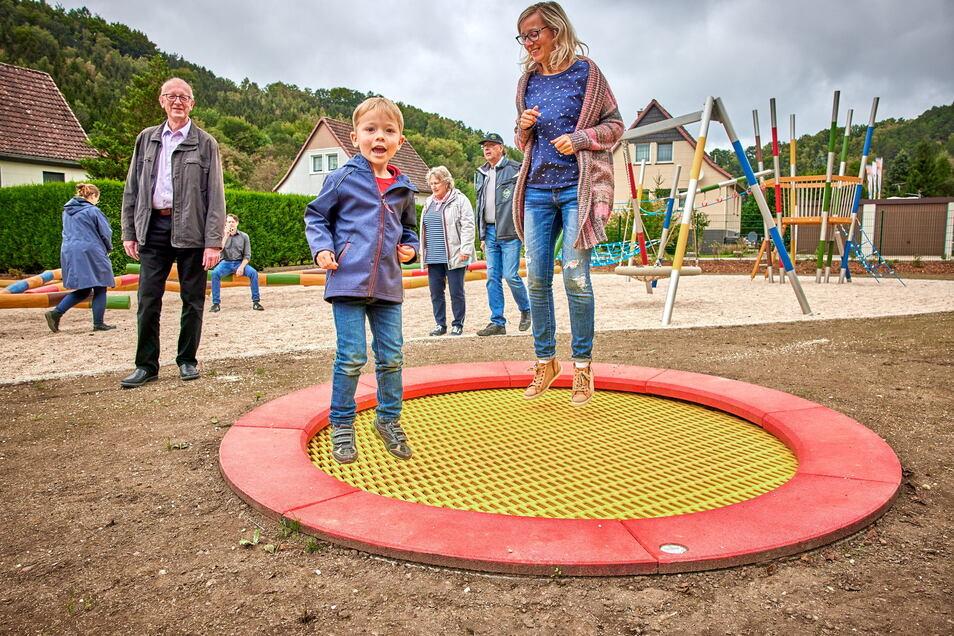 Luftsprünge vor Freude: Der 4-jährigen Lenny und Christina Benedix testen das Trampolin, Bürgermeister Uwe Thiele (li.) bleibt am Boden.