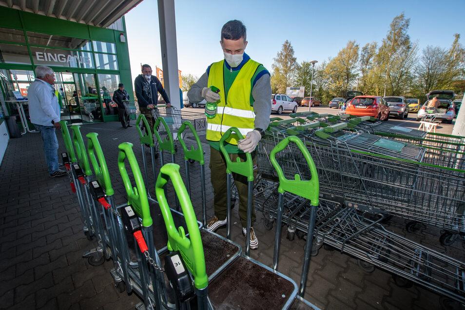 Mitarbeiter Luca Radke desinfiziert jeden Einkaufswagen nach der Benutzung der Besucher.