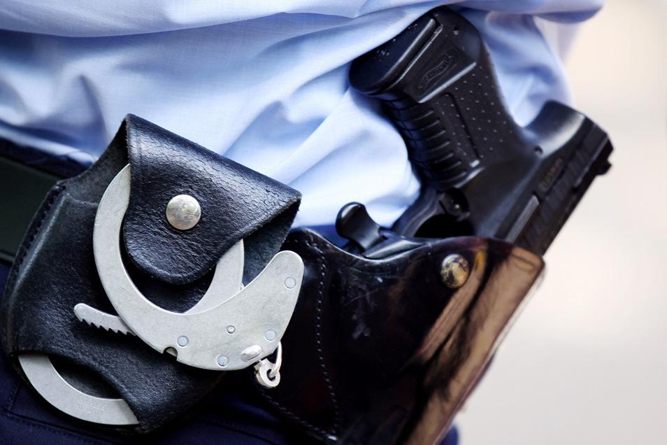 Ein Polizist trägt Handschellen und Pistole am Gürtel.