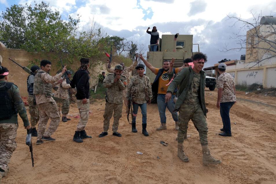 Mitglieder der Armee der libyschen Regierung, die von der UN unterstützt wird, halten ihre Waffen in die Luft.