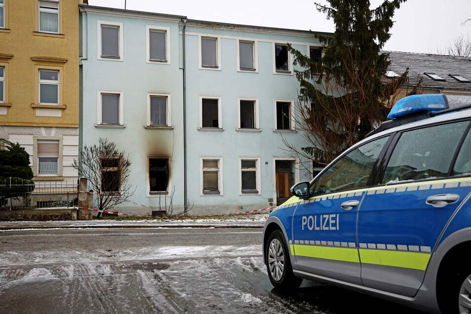 Die Polizei bewachte am Dienstag das Haus an der Pausitzer Straße, in dem es während der vergangenen Tage mehrfach gebrannt hatte.