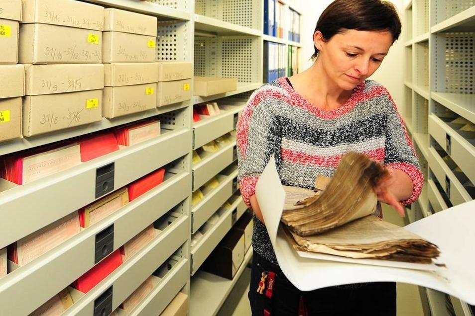 Archivarin Claudia Nowak zeigt Blätter aus dem Freitaler Aktenfund. Papiere, die sich mit der Ausreise aus der DDR befassen, wurden mikroverfilmt, sodass die Originale nicht benutzt werden müssen, um für Betroffene darin zu blättern.