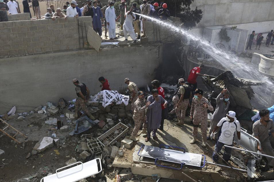 Soldaten und Frewillige bergen an der Absturzstelle Tote und versuchen ein Feuer zu löschen.