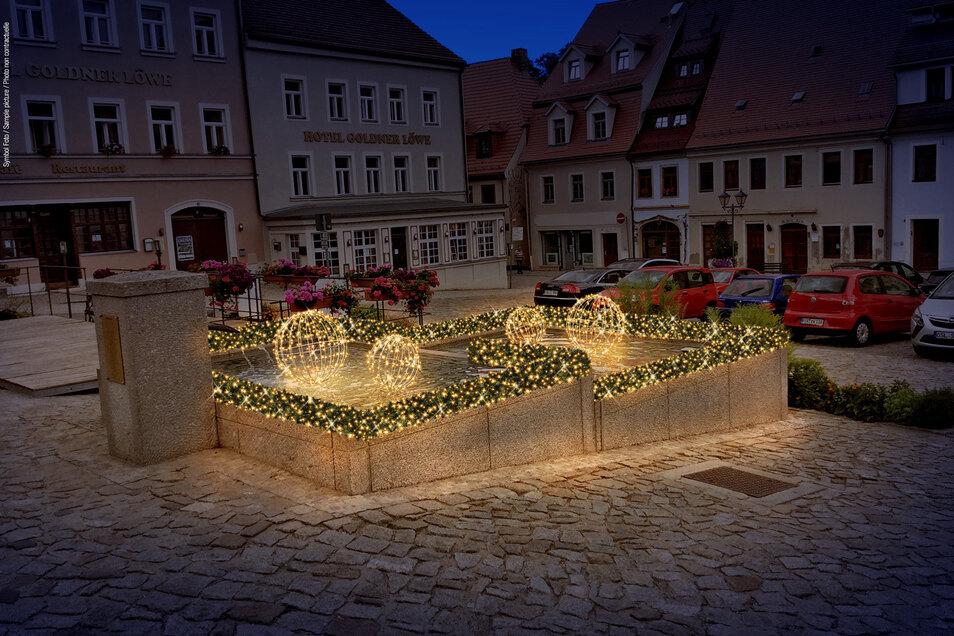 Die Fotomontage zeigt, wie der Brunnen auf dem Stolpener Markt in wenigen Tagen leuchten wird.
