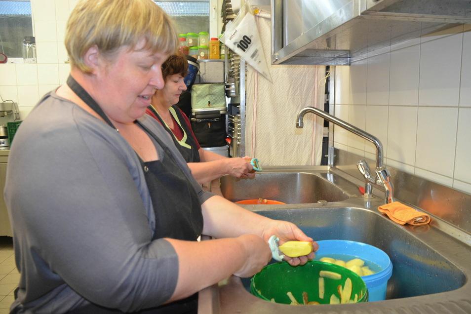 Mandy Plumrich (vorn) und Heike Schwerdtner schälen Kartoffeln im Akkord per Hand.