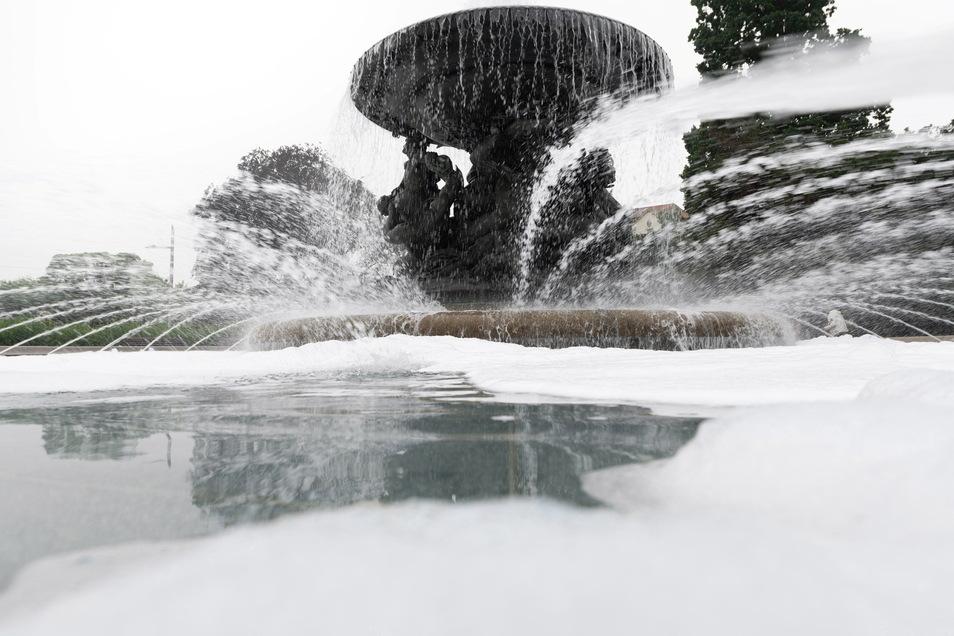 """Am Samstagmorgen treiben Schaumwolken auf dem Wasser im Brunnen """"Stürmische Wogen"""" am Albertplatz."""