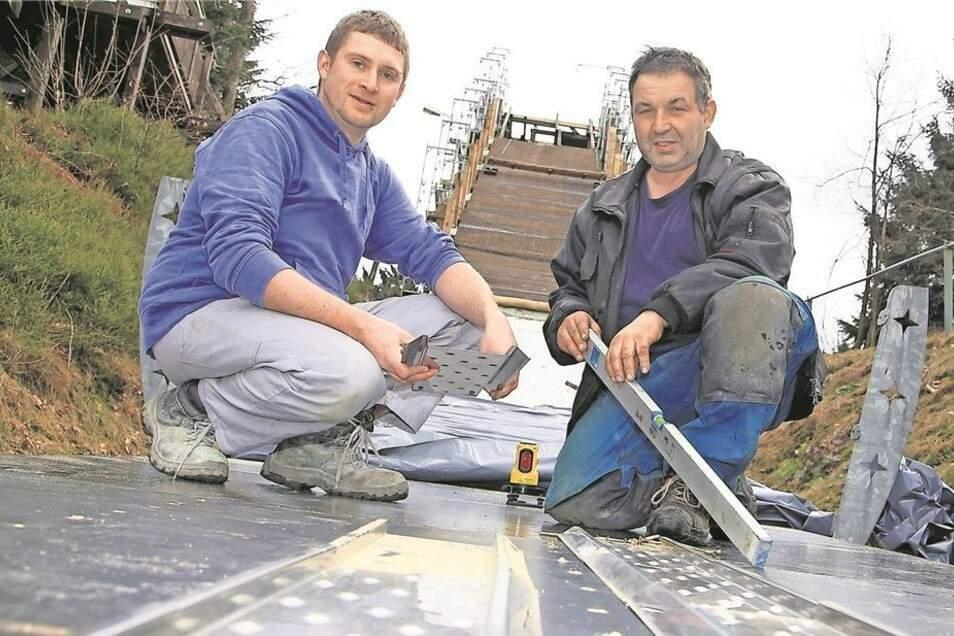 Bei der Schanzen-Rekonstruktion im Frühjahr 2015: Heiko Nitschke (rechts) und Björn Pallmer verlegen die Metallspuren, in denen die Skispringer jetzt wieder die Schanze hinabsausen.