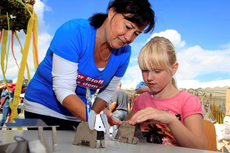 Bauern- und Handwerkermarkt: Kerstin Hinderer bastelt mit kleinen Gästen Miniaturen aus Metall.