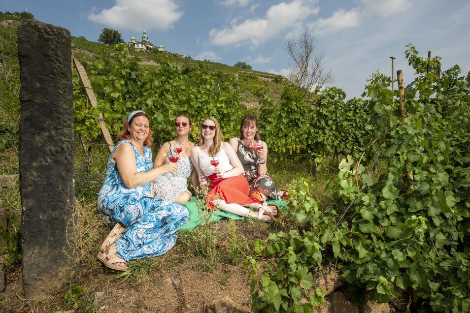 Andrea und Nele Hausmann sowie Liza und Andrea Nowak (v.l.n.r.) haben es sich auf einer Picknickdecke gemütlich gemacht. Sie genießen den Wein und die Aussicht.