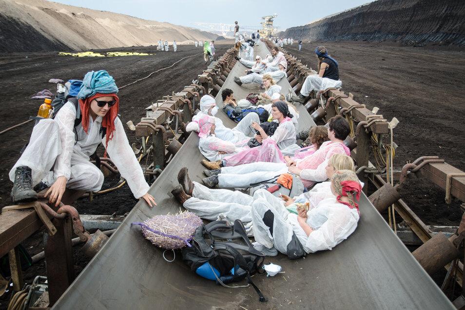 """Ein bild vom Mai 2016: Aktivisten des Protestbündnisses """"Ende Gelände"""" liegen auf einem Förderband im Tagebau Welzow. Die Proteste waren Teil einer weltweiten Aktionsreihe, die sich gegen die Nutzung fossiler Rohstoffe wie Kohle und Öl richtet."""