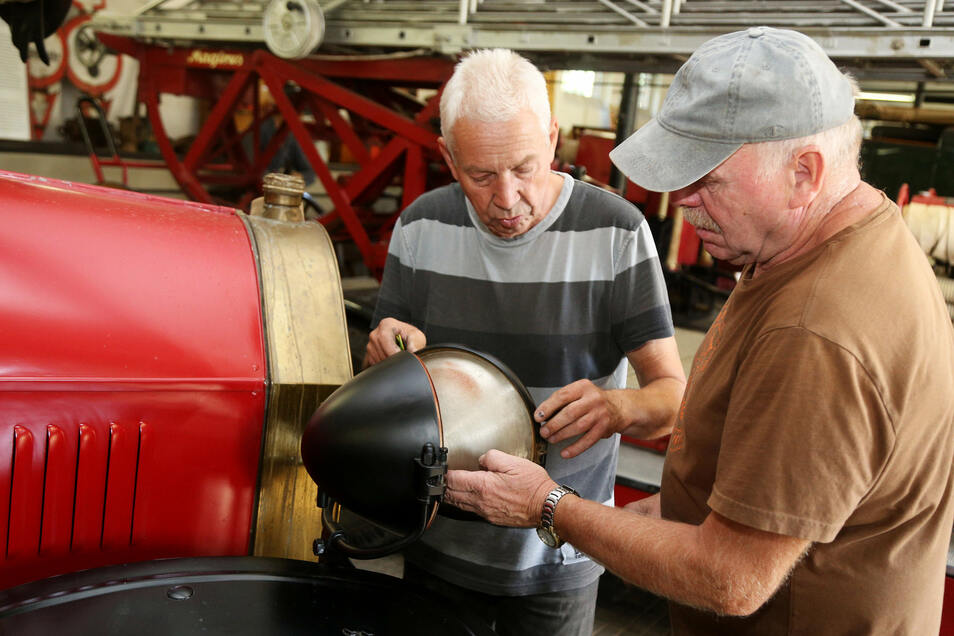 Gerd Langer (links) und Frank Zacharias reparieren die Lampe an einer Autospritze von 1920. Die Beiden gehören zu den vielen fleißigen Helfern der AG Feuerwehrhistorik, die das sächsische Landesfeuerwehrmuseum in Zeithain erst möglich gemacht haben.