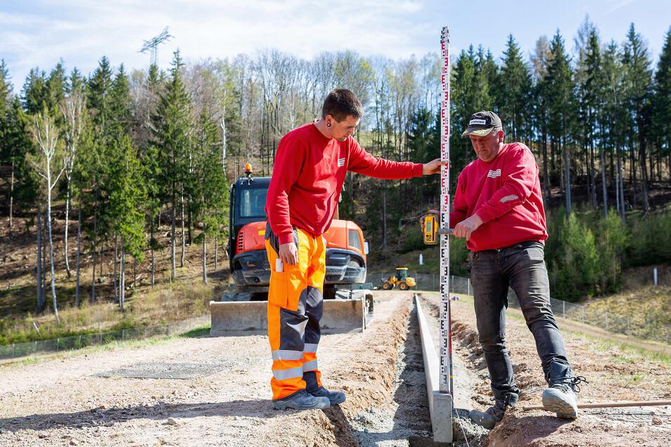 Matthias Bernhardt und Tom Bernhardt sichern hier mit einem Steinbord die Dammkrone am Prießnitzdamm in Glashütte, um weitere Setzungen zu vermeiden.