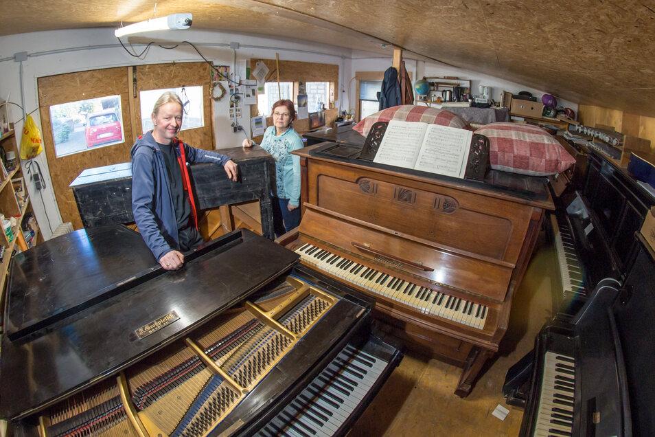 Orgelbauer und Klavierstimmer Johannes Soldan und seine Mitarbeiterin Astrid Zischank inmitten vieler Klaviere. Sie werden von ihm repariert und aufgearbeitet in seiner Werkstatt in Ödernitz