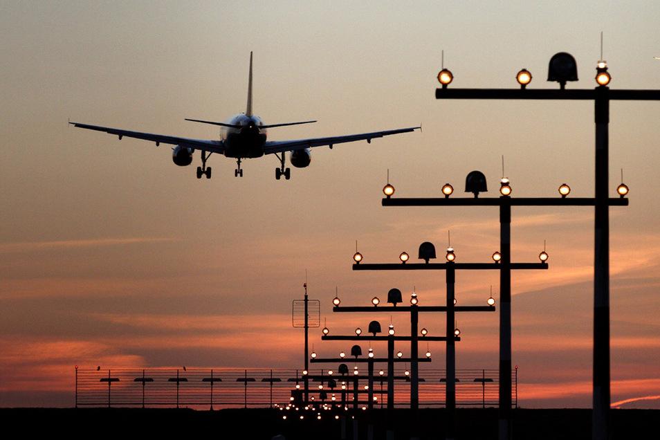 Ein Flugzeug ist während des Sonnenuntergangs im Landeanflug.