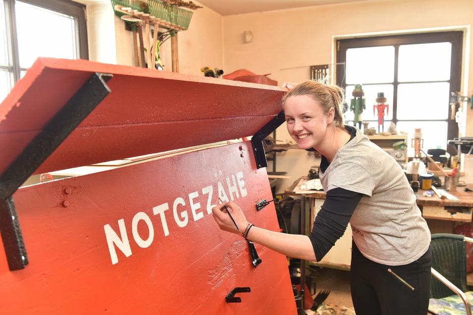 Elisabeth Bott arbeitet im Freiwilligenjahr im Altenberger Museum mit. Hier verpasst sie der Holztafel für das Notgezähe, an dem in der Grube Werkzeuge wie Schaufeln und Hacken hängen, - einen frischen Anstrich.