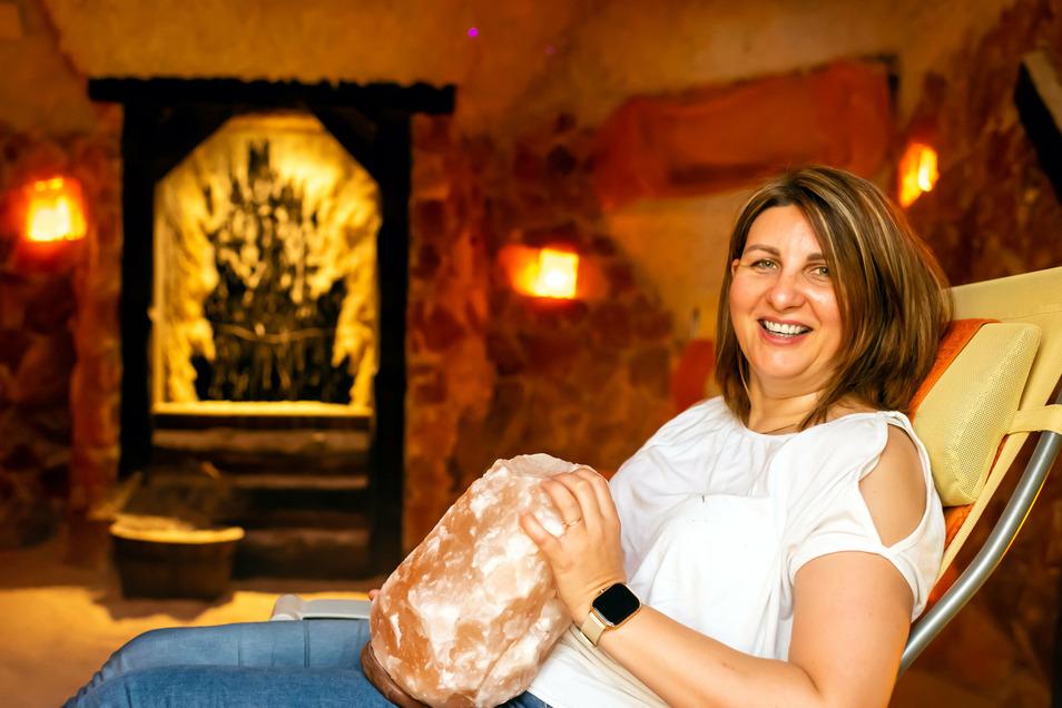 Sylwia Morales hat es sich ausnahmsweise mal selbst auf einer Liege in ihrer Salzgrotte Salina in Bautzen bequem gemacht und zeigt dabei eine Salzlampe, die für heimeliges Licht sorgt.