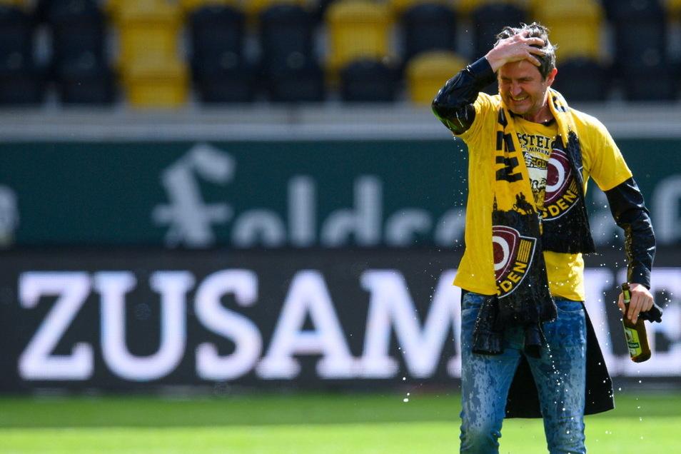 Eine Flasche Bier in der Hand und mindestens eine im Haar und auf dem Aufstiegs-T-Shirt: Dynamos Sportgeschäftsführer Ralf Becker feiert nach dem Abpfiff mit der Mannschaft im Stadion, erst später erfährt er, was davor wirklich los war.