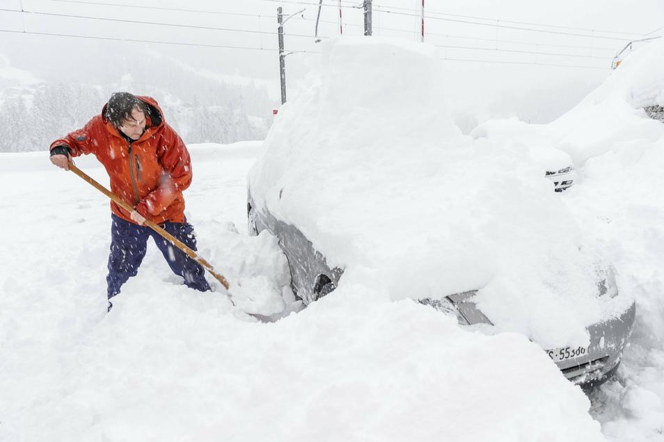 Ein Mann schaufelt in Fuergangen sein eingeschneites Auto frei. Viele Walliser Täler sind wegen dem starken Schneefall von der Außenwelt abgeschnitten.