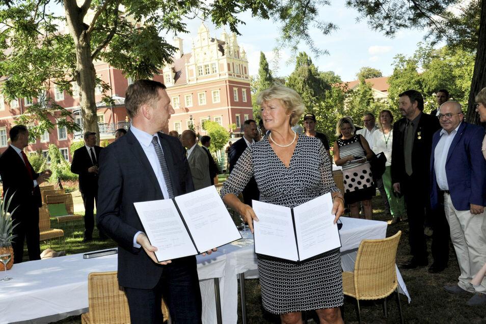 Michael Kretschmer und Monika Grütters präsentieren erleichtert und zufrieden die gemeinsam unterzeichneten Papiere zur weiteren Welterbe-Förderung.