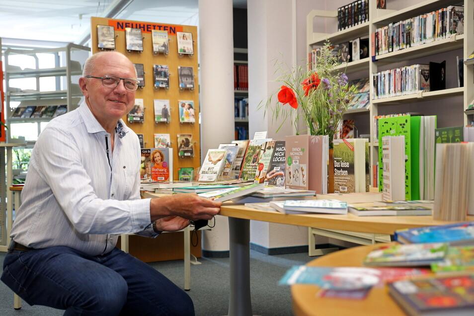Ullrich Bannorth, Geschäftsführer der Energiegesellschaft Riesa, vor den Büchern, die das Unternehmen der Bibliothek gesponsert hatte.