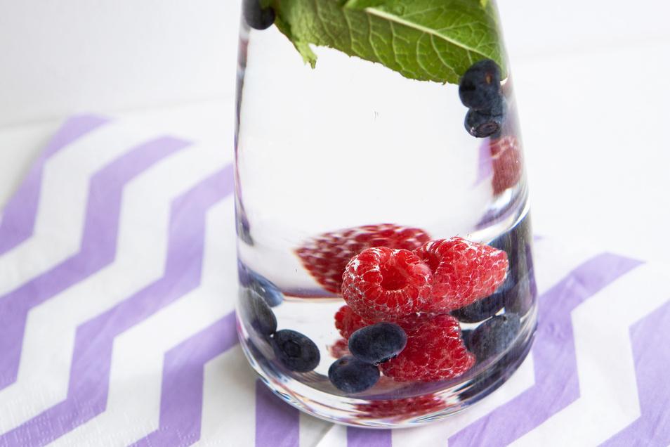 Bei Hitze ist mit Beeren und Minze versetztes Wasser besonders erfrischend: Aus Hygienegründen sollten Obst und Kräuter aber regelmäßig ausgewechselt werden.
