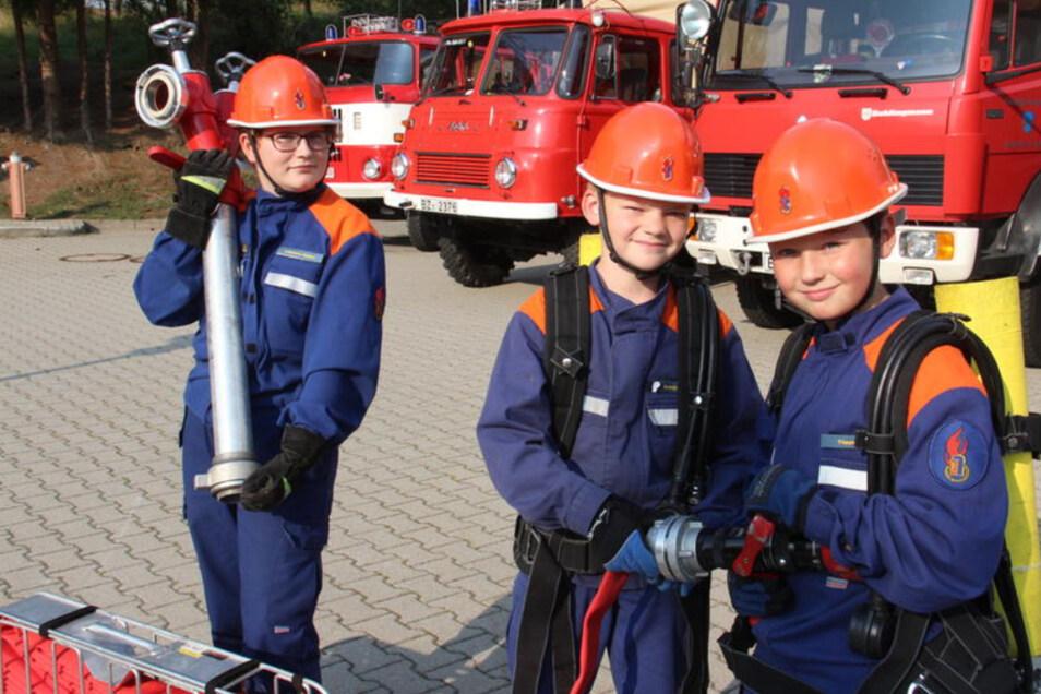 Nadine, Anton und Julius (v.l.) von der Jugendfeuerwehr Sohland bereiten sich auf die Schauübung vor, die am 8. September im Rahmen des Feuerwehrfestes stattfindet.