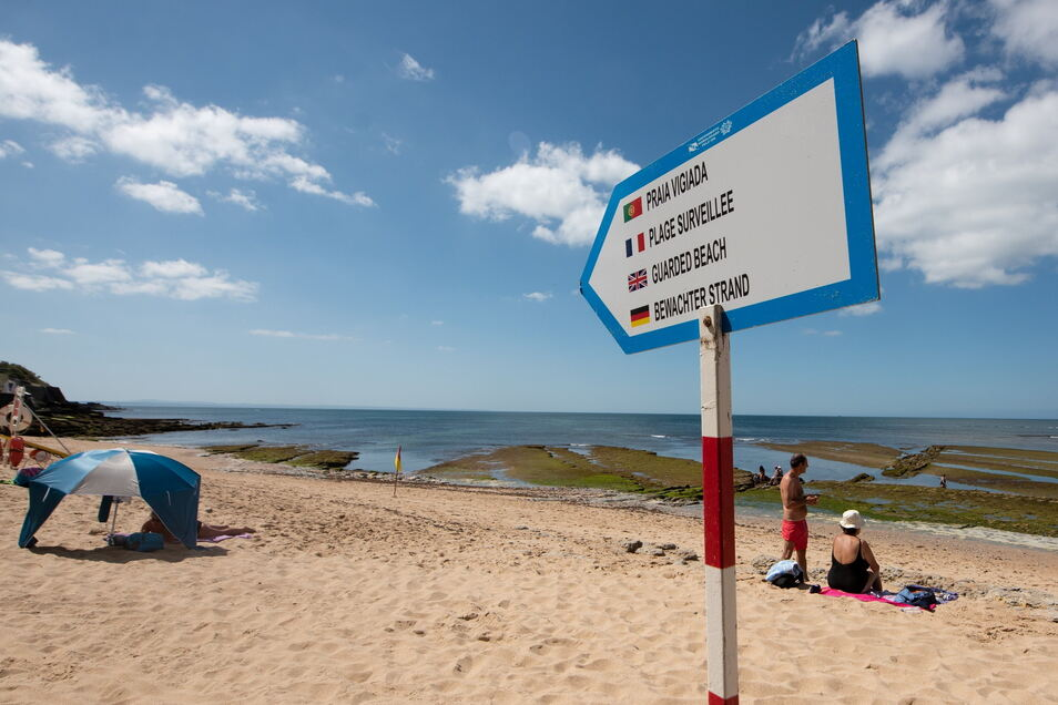 Ein Schild am Strand von Parede in Lissabon. Wer in Portugal Urlaub gebucht hat, der muss sich jetzt mit dem Stornieren auseinandersetzen.