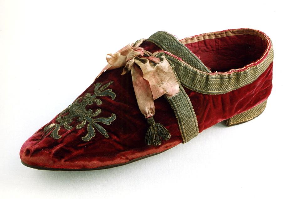 Zeremonialschuh von Papst Pius VII., der von 1800 bis 1823 im Amt war. Roter Seidensamt mit Goldstickerei verziert, ein elfenbeinfarbenes Schuhband und Goldquasten.