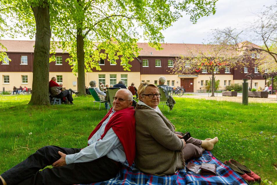 Angela und Hans Grobert sitzen Rücken an Rücken auf der Wiese vor den Parksälen in Dippoldiswalde. Sie genießen nach langer Corona-Durststrecke das Konzert sichtlich.