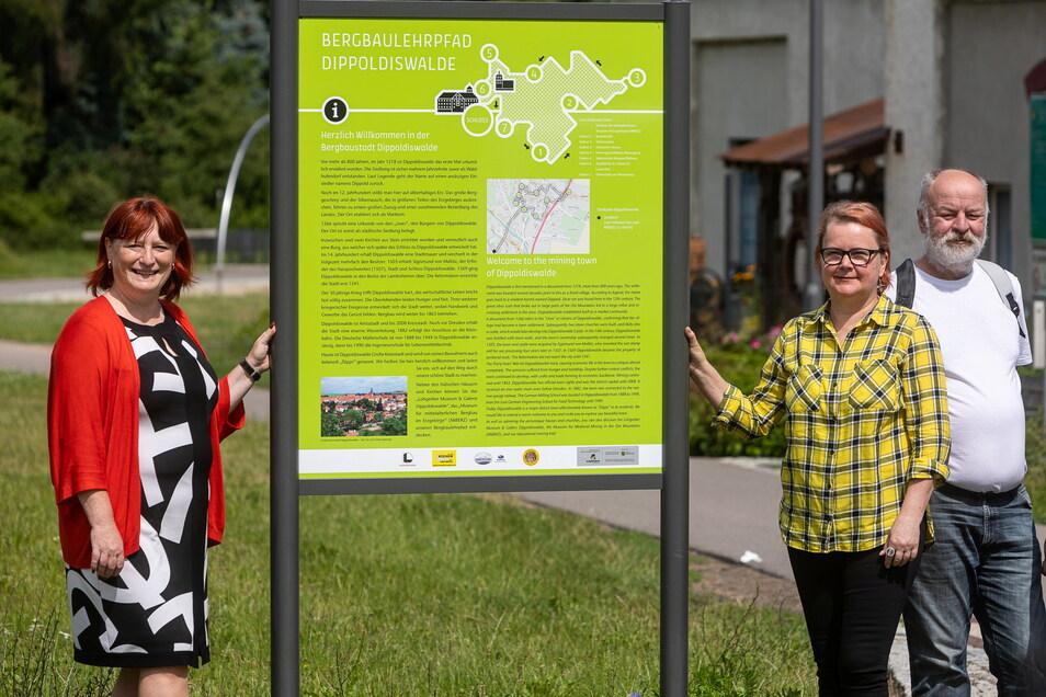 Dippoldiswaldes OB Kerstin Körner (li.) und Andrea Reichel, die Vorsitzende des Bergbau-Fördervereins in Dippoldiswalde, stehen mit anderen Vereinsmitgliedern an der neuen Tafel gegenüber vom Dippser Bahnhof.