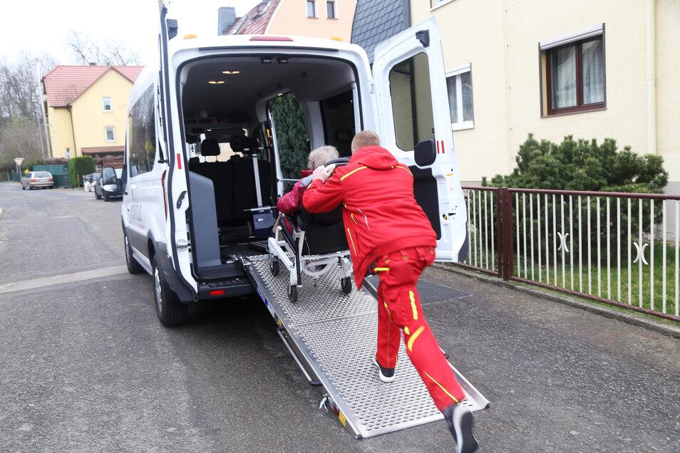 Über eine Rampe schiebt Nico Michael die Seniorin, die in einem Tragestuhl sitzt, in den Transporter. Wenig später hat die Frau einen Dialysetermin an der Kochstraße.
