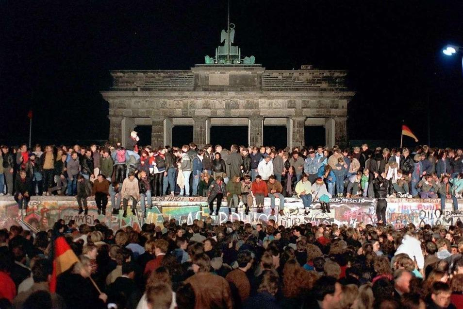 Am Brandenburger Tor wird die ganze Nacht gefeiert. Berliner aus Ost und West sind auf die drei Meter breite Panzermauer geklettert.